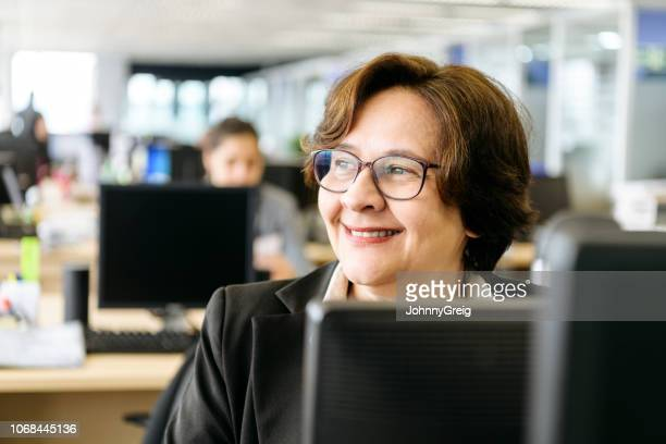 candid portrait of mature woman in office - office cubicle stock pictures, royalty-free photos & images