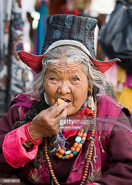 Candid portrait of old lady wearing traditional Ladahk clothing including hat, beads and robes. She has glasses resting on her forehead and is eating...