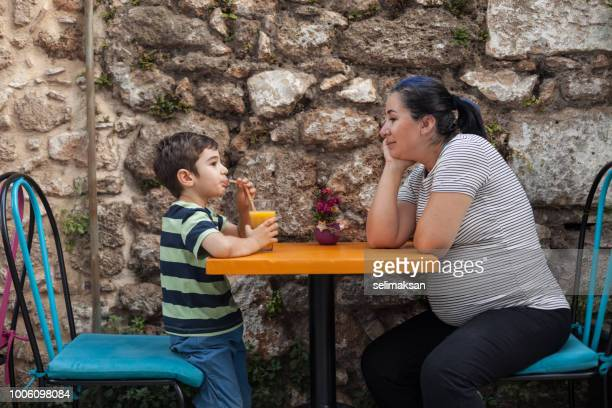 Candid Portrait Of Pregnant Woman And Her Son Sitting In Outdoor