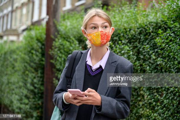 candid portrait of schoolgirl in face mask looking away - uniform stock pictures, royalty-free photos & images