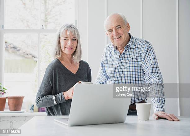 Candid portrait of senior man and woman with laptop