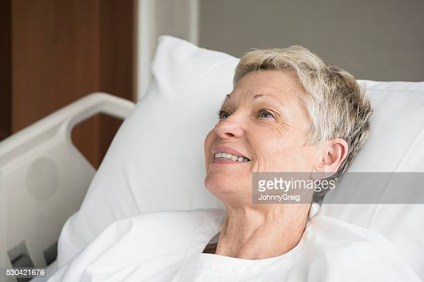Candid portrait of smiling senior woman in hospital bed