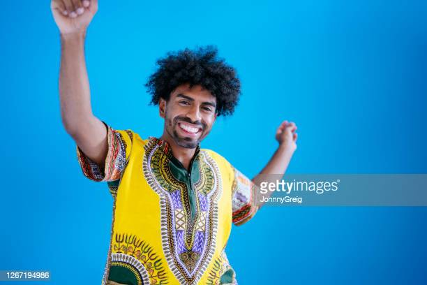 candid portrait of smiling young mixed race man dancing - short sleeved stock pictures, royalty-free photos & images