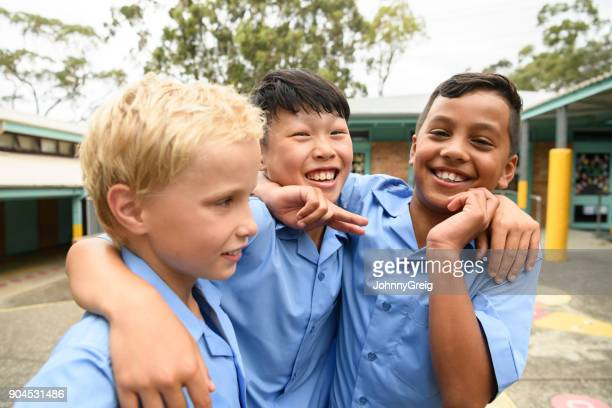 candid portrait of three boys in school playground with arms around each other - only boys stock pictures, royalty-free photos & images