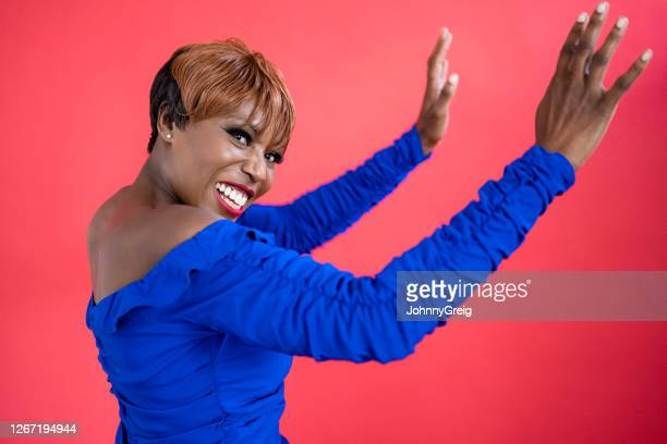 candid portrait of well-dressed mature black woman dancing - royal blue stock pictures, royalty-free photos & images
