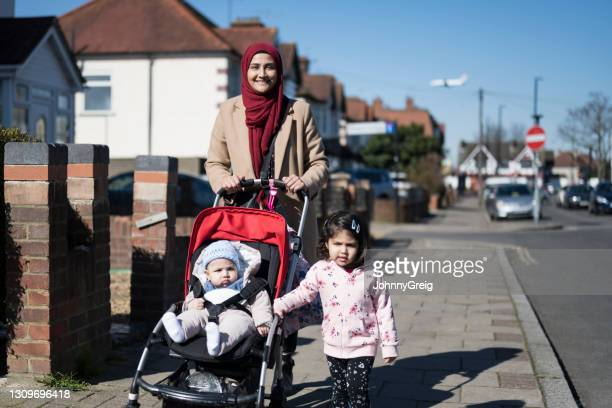 candid portrait of young british asian family on winter walk - religious dress stock pictures, royalty-free photos & images