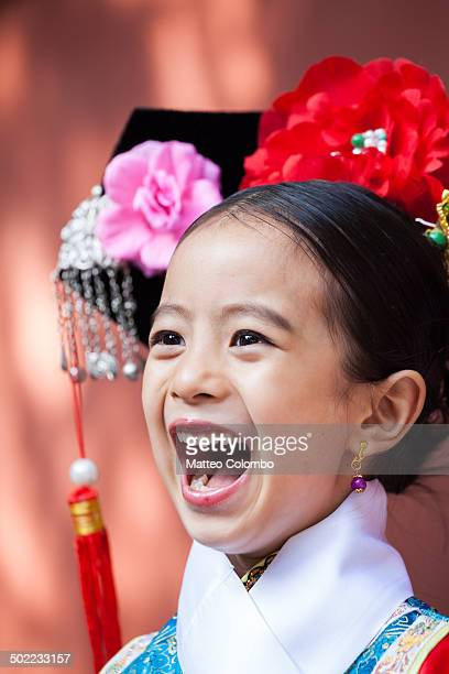 Candid portrait of young chinese girl smiling, wearing a traditional dress of imperial era. Summer palace complex, Beijing, China