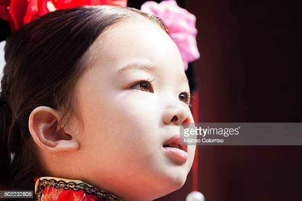 CONTENT] Candid portrait of young chinese girl with serious look wearing a traditional dress of imperial era Summer palace complex Beijing China