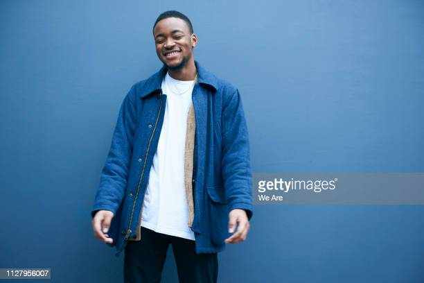 candid portrait of young fashionable man. - coloured background stock pictures, royalty-free photos & images
