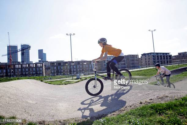 candid portrait of young female cyclist winning race on bmx track - bmx track london stock pictures, royalty-free photos & images