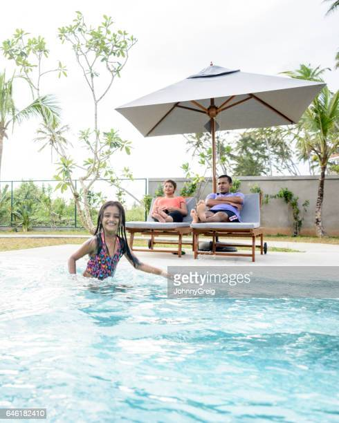 candid portrait of young girl in pool with parents sunbathing - girls sunbathing stock pictures, royalty-free photos & images