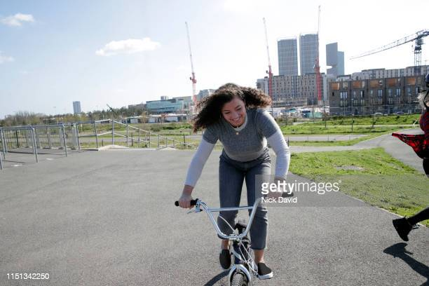 candid portrait of young woman cycling on a bmx bike - bmx track london stock pictures, royalty-free photos & images