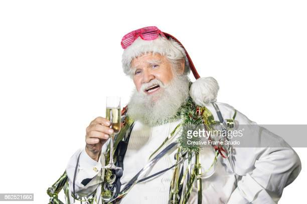 candid santa claus celebrating  with a glass of champagne and party favors - christmas card fotografías e imágenes de stock