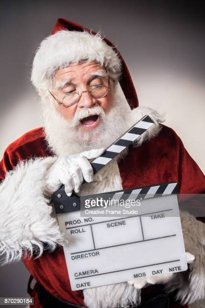Candid Santa Claus holding a film clapperboard