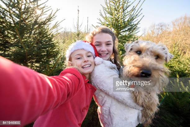 Candid selfie of girl in santa hat with her sister holding a dog