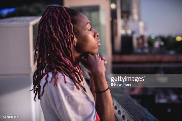 A candid shot of a fashionable, black woman with purple hair at sunset.