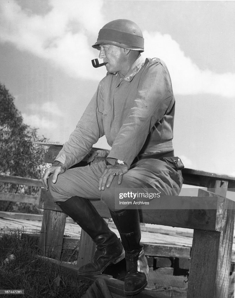 Candid shot of Major General George S. Patton, Jr., sitting on a fence and smoking a pipe, as he watches 3rd Army maneuvers in Louisiana, September 8, 1941.