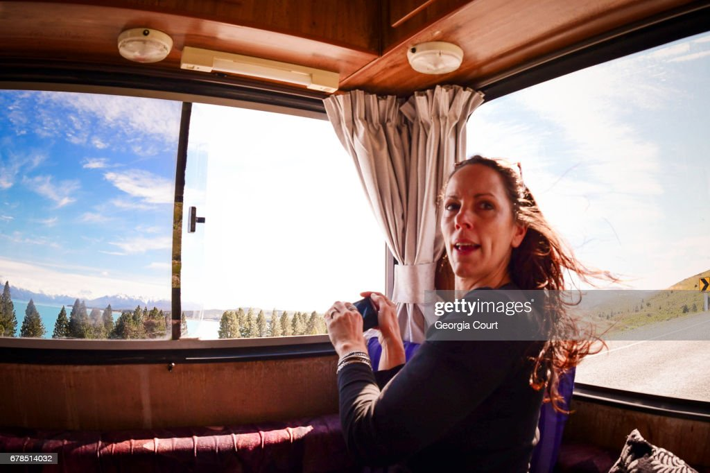 Candid shot of woman in back of retro motor home amazed at the view : Stock Photo