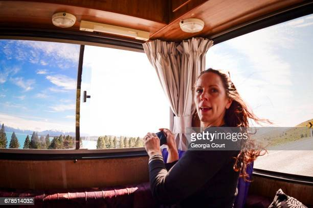 Candid shot of woman in back of retro motor home amazed at the view