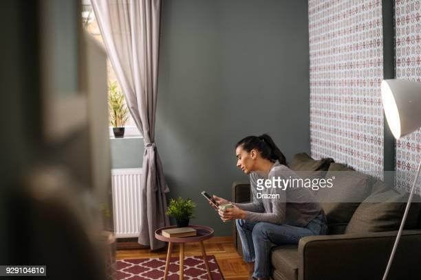 Reportageaufnahme Frau mit Smartphone zu Hause