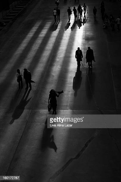 Candid silhouettes of people walking; classic black and white, vertical framed photo with shadow and light.