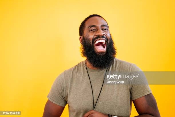 candid studio shot of laughing 31 year old black man - human face stock pictures, royalty-free photos & images