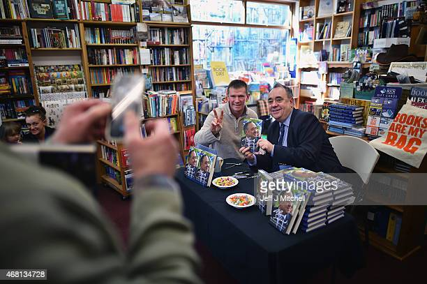 SNP candidate for the Gordon constituency Alex Salmond signs books during the first day of the British General Election campaign on March 30 2015 in...