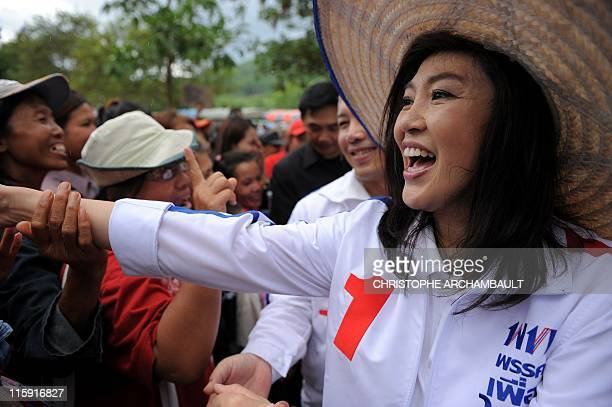 Candidate for the opposition Puea Thai party Yingluck Shinawatra the sister of former prime minister Thaksin Shinawatra walks through a crowd of...