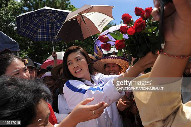Candidate for the opposition Puea Thai party Yingluck Shinawatra the sister of former prime minister Thaksin Shinawatra receives a bouquet of flowers...
