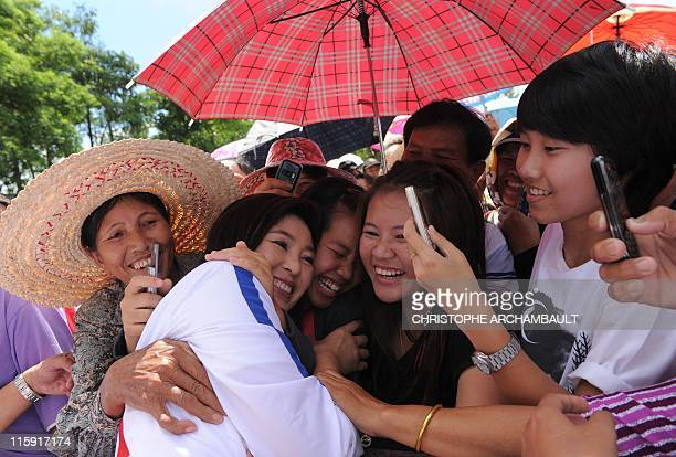 Candidate for the opposition Puea Thai party Yingluck Shinawatra the sister of former prime minister Thaksin Shinawatra receives hugs from supporters...