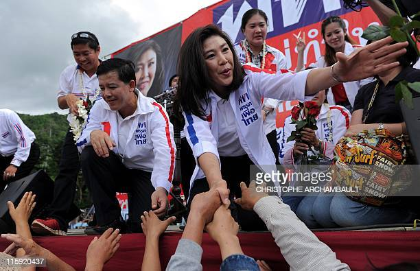 Candidate for the opposition Puea Thai party Yingluck Shinawatra the sister of former prime minister Thaksin Shinawatra extends her arms to shake...