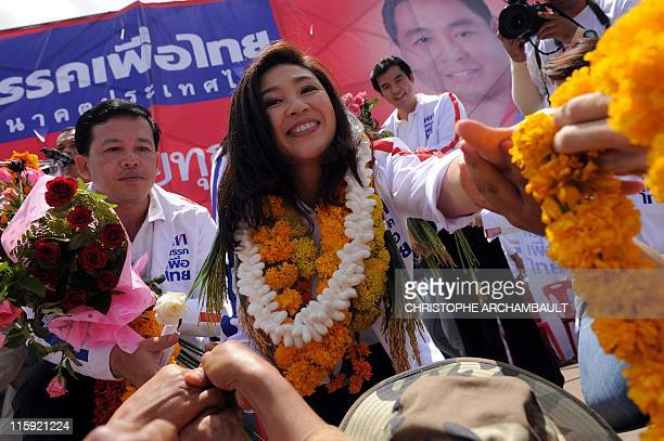 Candidate for the opposition Puea Thai party Yingluck Shinawatra the sister of former prime minister Thaksin Shinawatra extends her arms to receive...