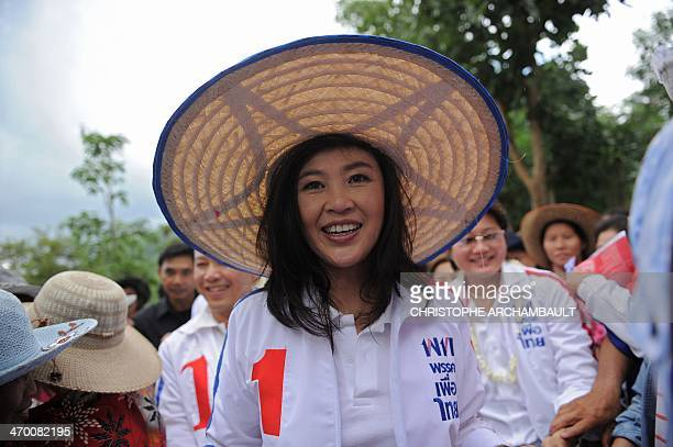 Candidate for the opposition Puea Thai party Yingluck Shinawatra the sister of former prime minister Thaksin Shinawatra smiles as she walks through a...