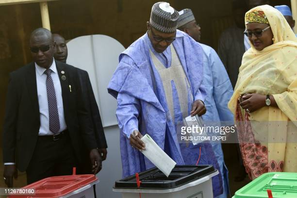 Candidate of the All Progressives Congress and incumbent President Muhammadu Buhari flanked by his wife Aisha Buhari casts his vote at a polling...