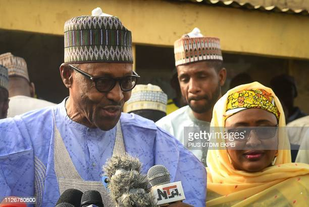 Candidate of the All Progressives Congress and incumbent President Muhammadu Buhari flanked by his wife Aisha Buhari speaks after voting at a polling...