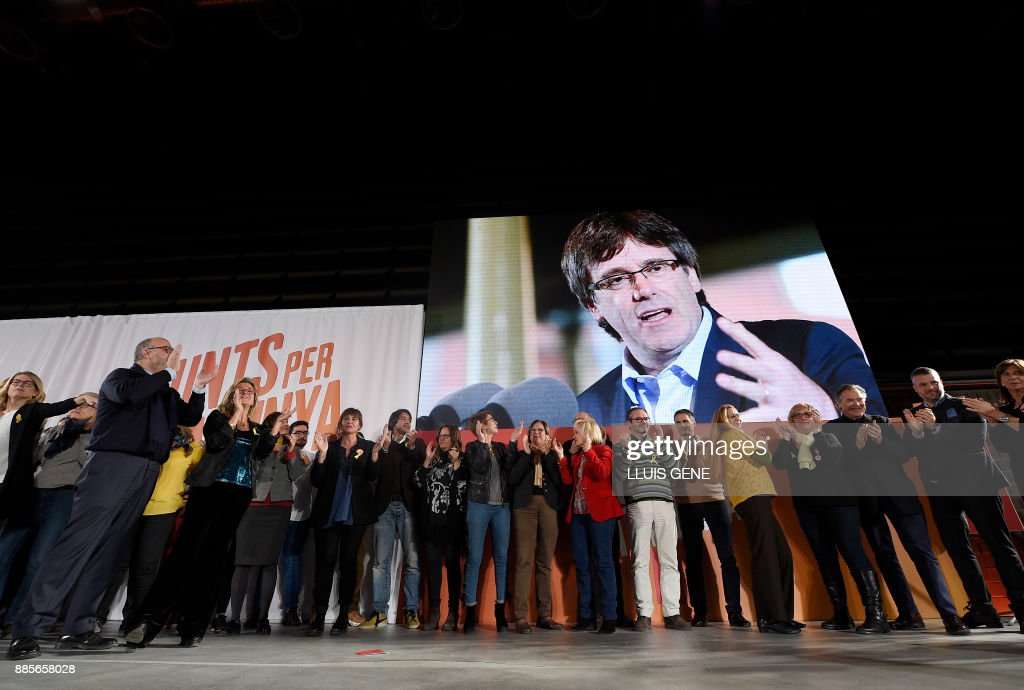 Candidates and members of 'Junts per Catalonia' (All for Catalonia) grouping applaud under a picture of their cadidate for the upcoming Catalan regional election, Carles Puigdemont, during the campaign opening meeting in Barcelona, on December 4, 2017. Catalans remain deeply split on independence, and several polls suggest pro-secession parties might struggle to win enough seats to form a new regional government after the December 21 regional election. GENE