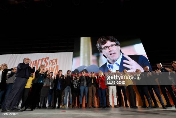 Candidates and members of 'Junts per Catalonia' grouping applaud under a picture of their cadidate for the upcoming Catalan regional election Carles...