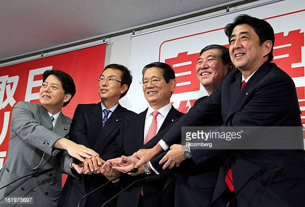 Candidates for leader of the Liberal Democratic Party shake hands during a joint news conference at the party's headquarters in Tokyo Japan on Friday...