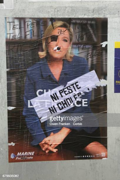 Candidates' posters on the street with Le Pen's face defaced as voters go to the polls in the second round of voting for President between candidates...