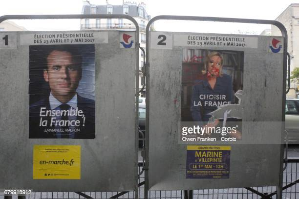 Candidates' posters on the street with Le Pen's face marked as voters go to the polls in the second round of voting for President between candidates...