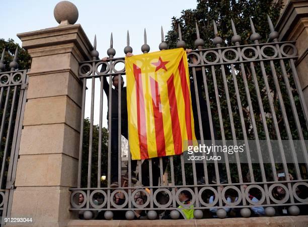 Candidatura d'Unitat Popular CUP parliament member Vidal Aragones hangs a Catalan proindependence 'Estelada' flag on the fence of the Catalan...