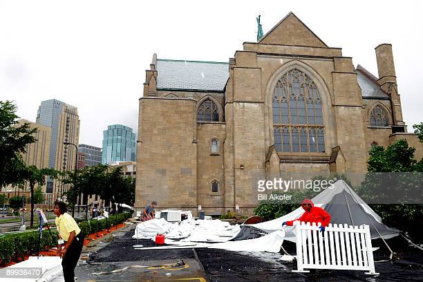 Candis McKelvy of the Minneapolis Convention Center helps clean up a temporary structure that was destroyed outside the Central Lutheran Church...