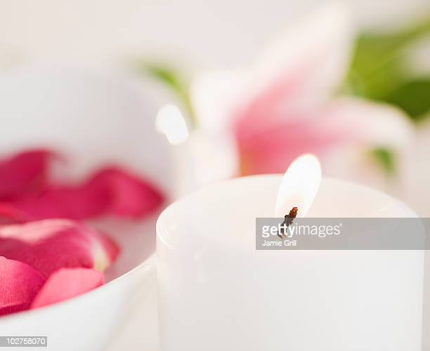 Candle and bowl of rose petals
