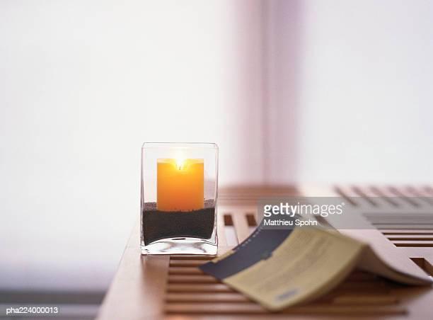 candle and open book on table inside. - cero foto e immagini stock