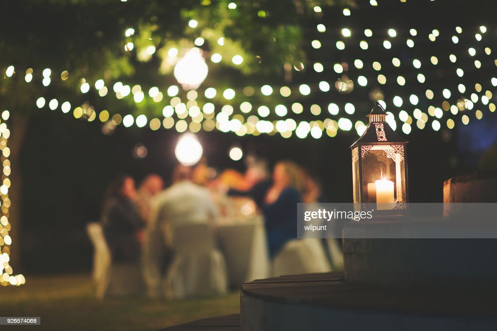 Candle and string lights outdoor dinner : Stock Photo
