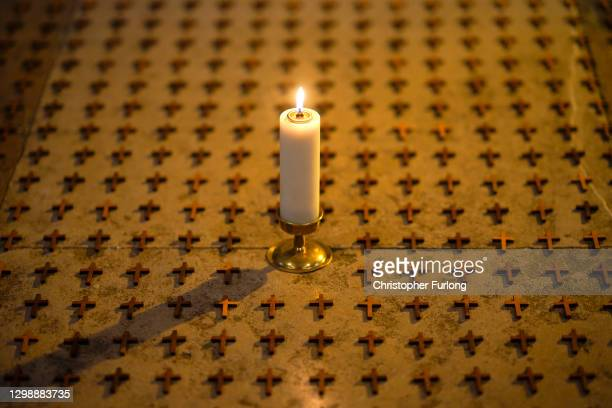 Candle blessed by the Bishop of Norwich stands amongst 1,000 crosses at Norwich Cathedral helping to remember the people of Norfolk who have died due...