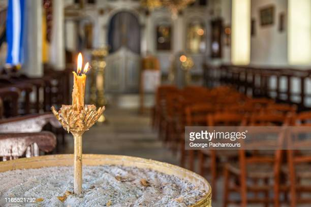 candle burning in greek orthodox church - greek orthodoxy stock pictures, royalty-free photos & images