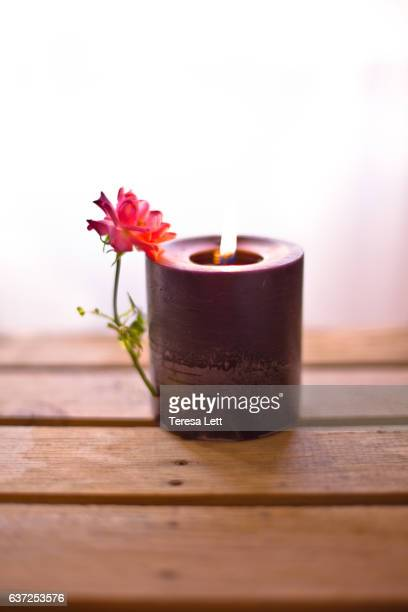 Candle burning with a rose