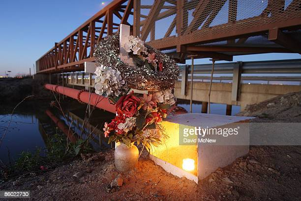 A candle burns at a roadside memorial cross next to an irrigation canal on April 17 2009 near Firebaugh California Central Valley farmers and farm...