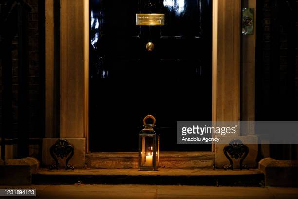 Candle burns in a remembrance lantern placed outside the door of 10 Downing Street as a 'National Day of Reflection' remembering victims of the...